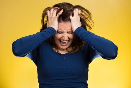 Gros plan portrait souligné femme d'affaires, tirant ses cheveux, criant, hurlant de crise de colère isolé sur fond jaune. Émotions humaines négatives, les expressions faciales, l'attitude de réaction