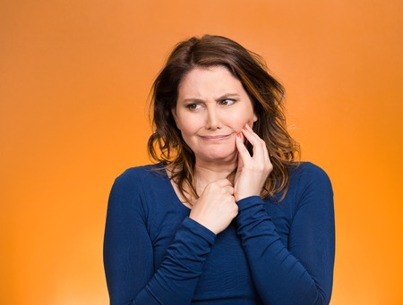 gingivitis: Portrait middle aged woman with sensitive tooth ache, crown problem crying from pain, touching outside mouth with hand isolated orange background. Negative emotion, facial expression feeling, health Stock Photo