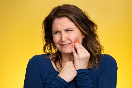 Portrait middle aged woman with sensitive tooth ache, crown problem crying from pain, touching outside mouth with hand isolated yellow background. Negative emotion, facial expression feeling, health photo