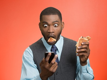 surprised man: Portrait surprised, corporate business man holding, reading bad news on smart phone, eating cookie about to choke isolated red background. Funny looking face expression emotion unexpected reaction
