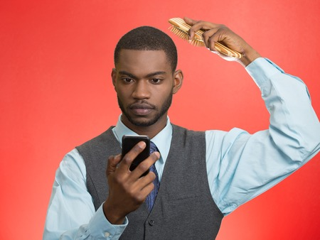 combing hair: Portrait serious business man, corporate executive reading news, e-mail on smart phone, combing  hair isolated red background. Human face expression, emotion, phone addiction concept