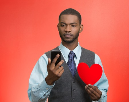 Portrait serious, thoughtful young man reading news, text message on smart phone, holding red heart isolated red background. Human facial expression, emotion feeling, body language. Social media photo