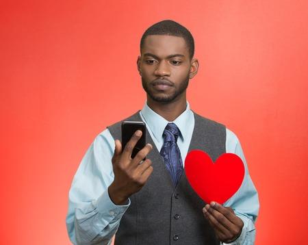expresion corporal: Retrato hombre serio, reflexivo joven la lectura de noticias, mensajes de texto en el teléfono inteligente, con corazón rojo aislado fondo rojo. La expresión humana facial, sensación de emoción, el lenguaje corporal. Los medios sociales Foto de archivo