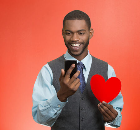 Closeup portrait cheerful young man looking at his smart phone, holding red heart in his hand, isolated red background. Human facial expressions, emotions, feelings, body language, life perception photo