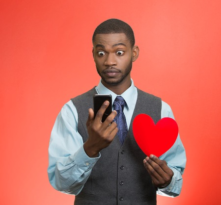 Portrait shocked young man, guy reading breaking news on smart phone holding red heart in his hand isolated red background. Human facial expression emotion feeling body language unexpected reaction photo