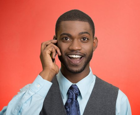 Headshot, portrait happy business man, young guy talking on mobile phone smiling isolated red background. Positive human facial expressions, emotions, feelings, life perception, attitude, thinking photo