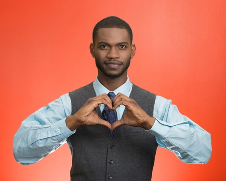 Portrait handsome smiling young business man makes hand heart shape using fingers isolated red background. Positive human emotions, facial expressions, feelings, body language, attitude photo