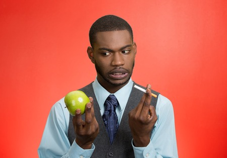 preventive: Stressed businessman deciding on healthy life choices, craving cigarette versus green apple isolated red . Face expression, body language, bad, hazardous human habits Stock Photo