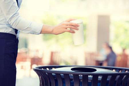 cesto basura: Primer mano de la mujer imagen recortada tirar papel vacío taza de café en la papelera de reciclaje, aislado exterior, los árboles de fondo. Reciclaje, enfoque respetuoso del medio ambiente concepto. Mantenga calles, ciudad, limpia la tierra