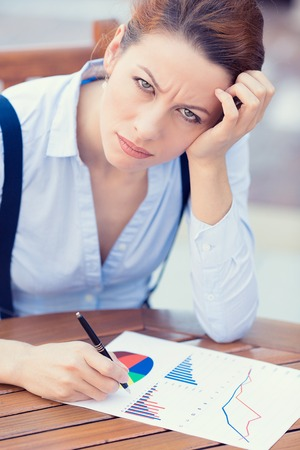 stockholder: Closeup portrait unhappy business woman looking displeased working on financial report stockholder meeting siting at table documents, writing, distressed, isolated outside. Negative expression emotion