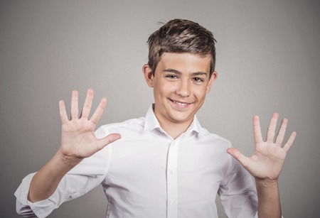 non verbal: Closeup portrait happy, smiling young man making five times sign gesture with two hands, fingers, isolated grey wall background. Positive human emotion, facial expression, feelings, attitude, symbol