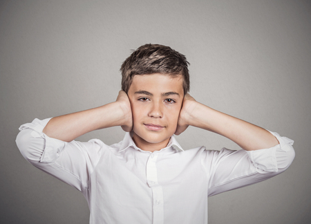 wrongful: Closeup portrait teenager boy covering ears with hands, doesnt want to hear loud noise, conversation isolated grey wall background. Human face expression, emotion, feeling reaction perception