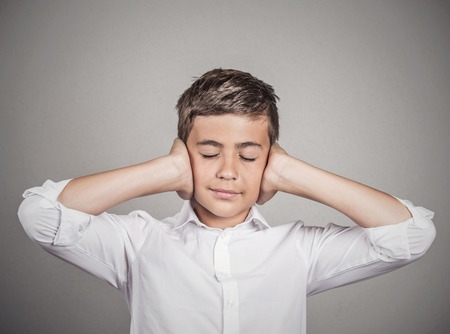 loud noise: Closeup portrait teenager boy covering ears with hands, doesnt want to hear loud noise, conversation isolated grey wall background. Human face expression, emotion, feeling reaction perception