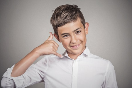 non verbal: Closeup portrait young man, handsome happy guy, teenager making call me gesture sign with hand shaped like phone, isolated grey wall background. Positive human emotions, face expressions