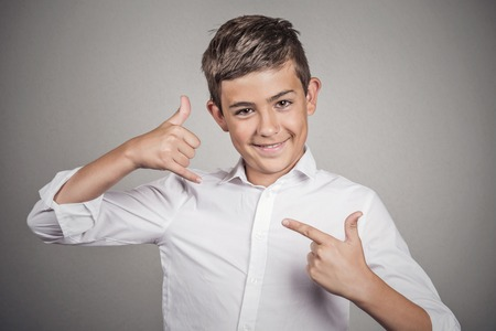 answering: Closeup portrait young man, handsome happy guy, teenager making call me gesture sign with hand shaped like phone, isolated grey wall background. Positive human emotions, face expressions