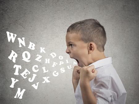 Vista lateral retrato niño enojado gritando, las letras del alfabeto que sale de su boca, aislado fondo de la pared gris. Expresiones negativas humanos cara, emoción, reacción. Conflicto, concepto confrontación