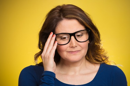 sorry: Closeup portrait, mature woman, shy, sad, playing nervously with glasses looking down, feeling guilty, sorry for actions, faults, did wrong, isolated yellow background. Expression, emotion, reaction Stock Photo