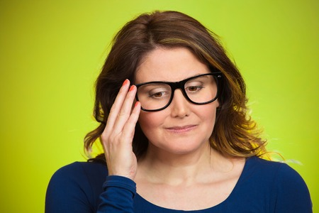 Closeup portrait, mature woman, shy, sad, playing nervously with glasses looking down, feeling guilty, sorry for actions, faults, did wrong, isolated green background. Expression, emotion, reaction photo