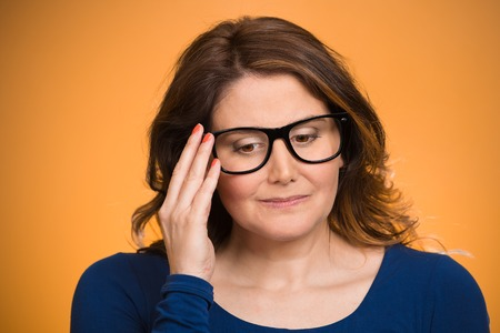 Closeup portrait, mature woman, shy, sad, playing nervously with glasses looking down, feeling guilty, sorry for actions, faults, did wrong, isolated orange background. Expression, emotion, reaction photo