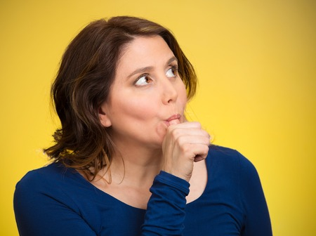 postpone: Closeup portrait middle aged woman with finger in mouth, sucking thumb, biting fingernail in stress, deep thought, isolated yellow background. Negative emotion facial expression feeling, body language Stock Photo