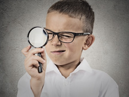 Curious child, boy looking through a magnifying glass, isolated grey wall background. Curiosity concept. Face expressions, life perception, discovery photo