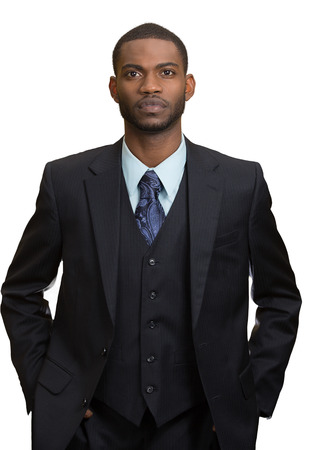ethnic attire: Confident employee. Closeup portrait Serious young business Man in full suit keeping arms in pockets, looking at camera, isolated white background. Human face expression, emotion, body language Stock Photo