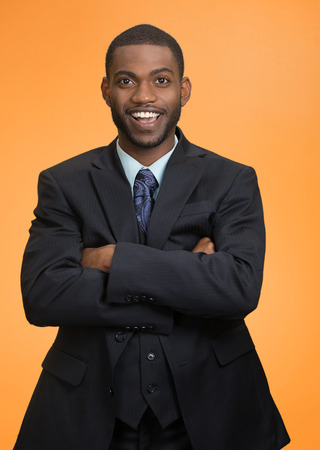 business attire teacher: Confidence, charisma. Portrait Cheerful handsome young african american man in full suit keeping arms crossed looking at camera isolated orange  background. Human face expression emotion body language