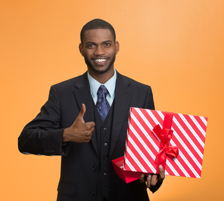 posing  agree: Portrait young happy, smiling business man holding present, red gift box, giving thumb up isolated orange background. Positive facial expression, human emotion body language, life perception attitude