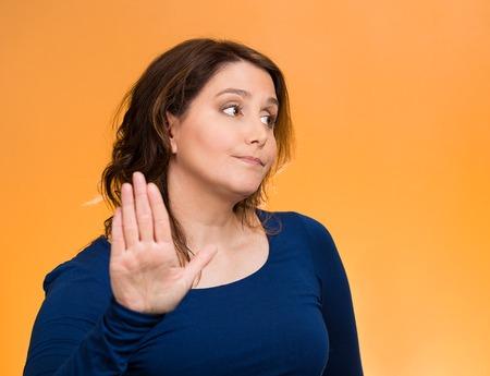 Close-up portret van middelbare leeftijd, knorrige vrouw met slechte houding, waardoor praten met mijn hand gebaar met palm naar buiten, geïsoleerde oranje achtergrond. Negatieve emoties, mimiek gevoelens, lichaamstaal