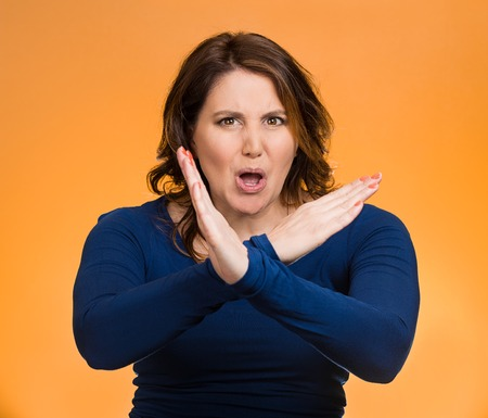 admonish: Portrait angry middle aged woman with X gesture to stop talking, cut it out, dont go there, isolated orange background. Negative human emotion facial expression feelings, signs symbols, body language