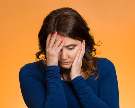unwanted: Closeup portrait sad, depressed, stressed, thoughtful young woman, full of worries, looking down, isolated orange background. Human face expressions, emotions, feelings, reaction, attitude, perception