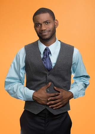 Portrait guy with stomach pain, miserable, upset, ill, unhealthy, young man, doubling over, looking very sick unwell isolated orange background. Facial expressions, emotions, reaction health issues photo