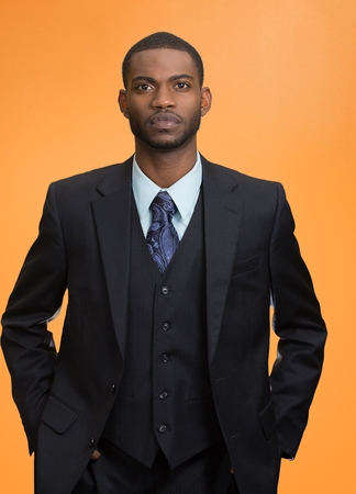 ethnic attire: Confident employee. Closeup portrait Serious young business Man in full suit keeping arms in pockets, looking at camera, isolated orange background. Human face expression, emotion, body language