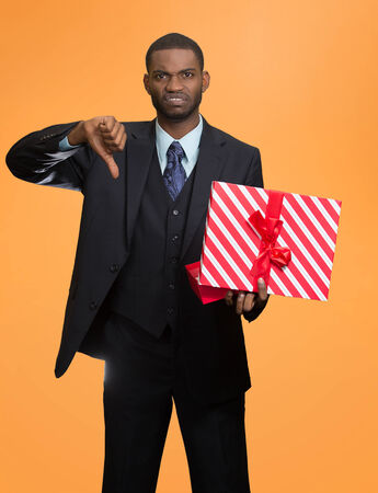 Grumpy unhappy upset man holding gift box displeased, showing thumbs down, disgust on face, isolated orange background. Negative human emotions, facial expressions, feeling attitude, body language photo