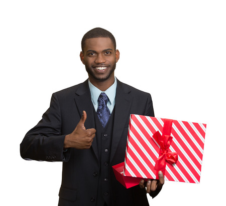 christmas bonus: Portrait young happy, smiling business man holding present, red gift box, giving thumb up isolated white background. Positive facial expression, human emotion body language, life perception attitude