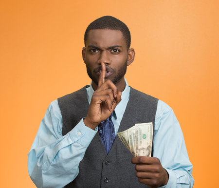 shutup: Portrait corrupt guy, businessman holding dollar bills in hand showing shhh sign finger to lips isolated orange background.