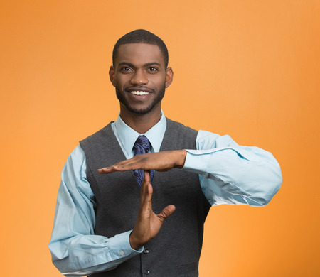 Portrait young, happy executive company man showing time out gesture with hands, isolated orange background.  photo