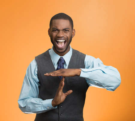 non verbal: Portrait angry young business man showing time out gesture with hands, screaming to stop isolated orange background.