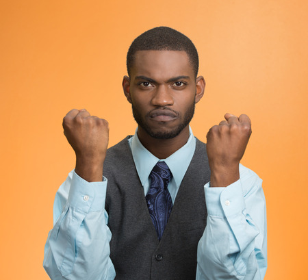 cranky: Portrait angry cranky upset pissed off man, worker, business employee putting up fist ready to give knuckle sandwich isolated orange background.