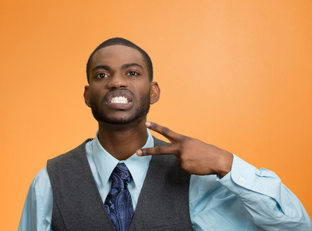 cut off head: Portrait angry young man gesturing with hand to stop talking, cut it out, or he will take your head off isolated orange background.  Stock Photo
