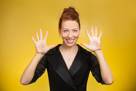 five fingers: Portrait happy, smiling young woman making, showing five times sign gesture with two hands, fingers, isolated yellow background. Positive human emotion, facial expression, feelings, symbol, non verbal communication