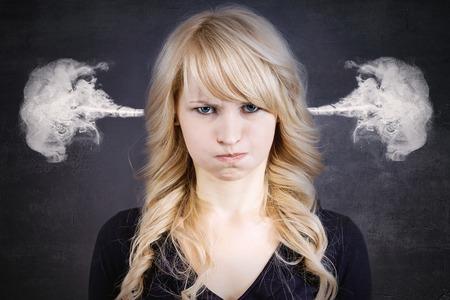 mujer enojada: Retrato del primer de la mujer joven enojado, vapor soplado que sale de las orejas, a punto de tener descomposici�n at�mica nervioso, aislado fondo negro. Emociones humanas negativas expresi�n facial sentimientos actitud Foto de archivo