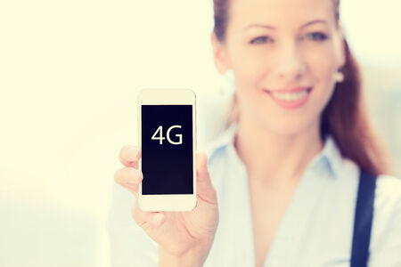 4g: Smiling female holding mobile smart phone with 4G sign on screen isolated outside city background focus on smartphone. New gadget technology, connection concept. Positive human emotion face expression Stock Photo