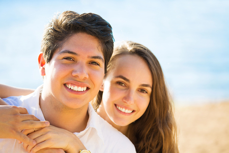 Portrait young beautiful smiling couple by the sea on a sunny summer, autumn day.  Positive human emotions, facial expressions, feelings, life perception. Happy lifestyle, romantic getaway photo