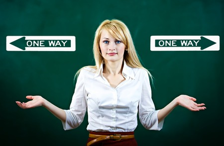 Portrait confused young woman shrugs shoulders, not sure which way, where go in life, isolated green background, with direction signs. Emotion, facial expression, feeling, reaction perception photo