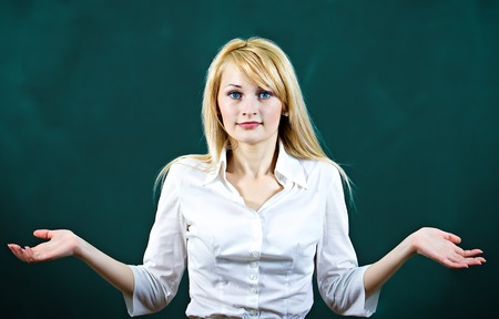 whining: Portrait clueless, unhappy young blonde woman with arms out asking whats the problem who cares, so what, I dont know. Isolated dark blue background. Negative human emotions facial expression Stock Photo