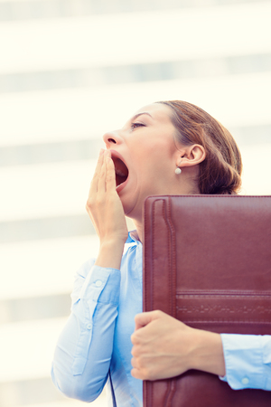 Its is too early for this meeting. Closeup portrait sleepy young business woman, running to work wide open mouth yawning, eyes closed looking bored isolated outside corporate office windows background photo