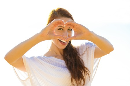 body heart: Happy beautiful young woman shows heart shape hands on summer, autumn, sunny day outside oceanside background. Positive human emotions, fax expressions, feelings, body language, life perception