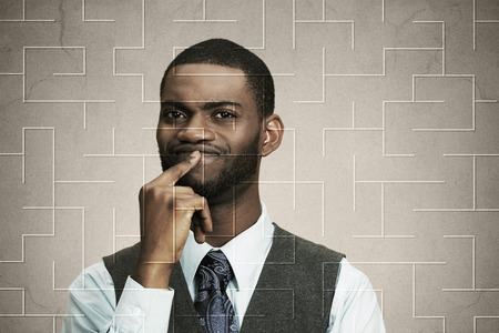 hard to find: Closeup portrait puzzled serious business man thinking hard how find right solution, direction, exit, finger on lips gesture isolated maze background. Human face expressions, body language perception Stock Photo