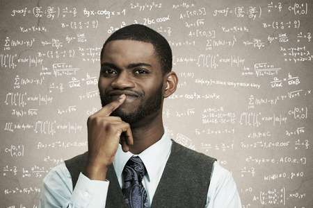 Closeup portrait young confused business man finger on lips, thinking deeply about something, looking puzzled, isolated black, grey background math formulas. photo